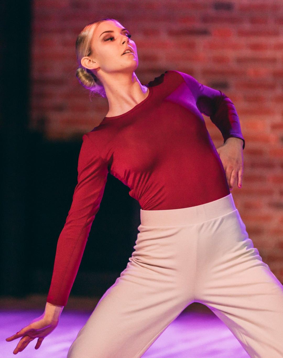 Tanssija seisoo tanssiasennossa mustat housut ja ruskea paita yllään.